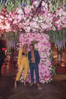 Celebrities Pose With The Flower Backdrop
